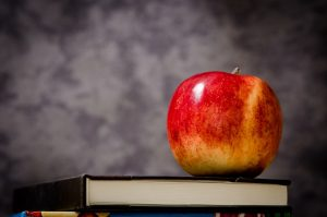 An image of an apple on top of a stack of books