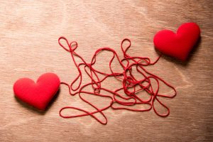 two hearts made of yarn connected together