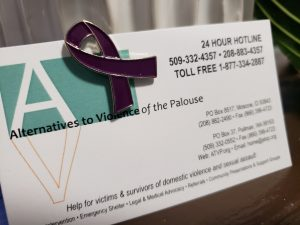 photo of Alternatives to Violence of the Palouse with text of contact information and purple ribbon pin attached to card