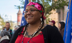 Tai Simpson's headshot; she is smiling off to the distance outside in the middle of a crowd with a red shirt and black cardigan, hair in pigtails, and embroidered pink headband.