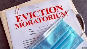 manila folder with paper that says eviction moratorium in red, all caps, at the top and a disposable mask laying on top