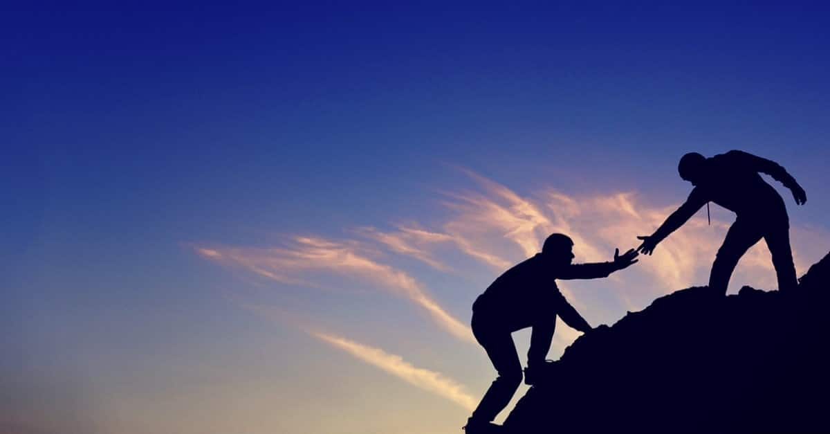 Silhouette of a person on a hill stretching out arm to help pull up another silhouetted person up the hill