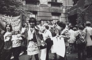 People smiling holding Pride signs